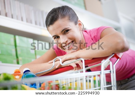 Young woman in pink shirt leaning to a shopping cart at supermarket. - stock photo