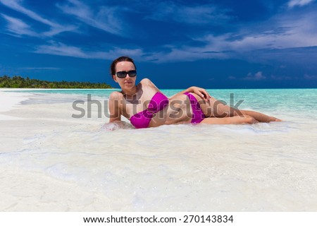 Young woman in purple bikini covered lying sand on tropical beach - stock photo