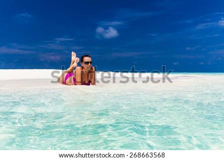 Young woman in purple bikini relaxing on white sand on tropical beach - stock photo