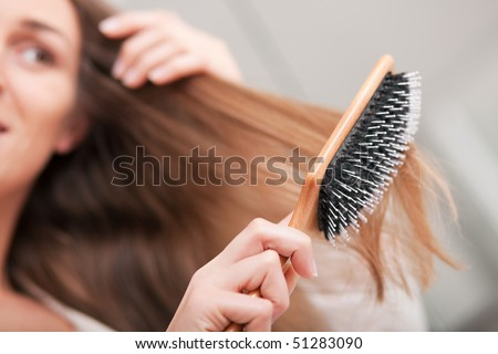 Young woman in pyjama brushing her long dark-blond hair after getting up in the morning; focus on brush! - stock photo