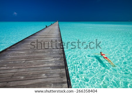 Young woman in red bikini swimming next to jetty in azure water of Maldives - stock photo
