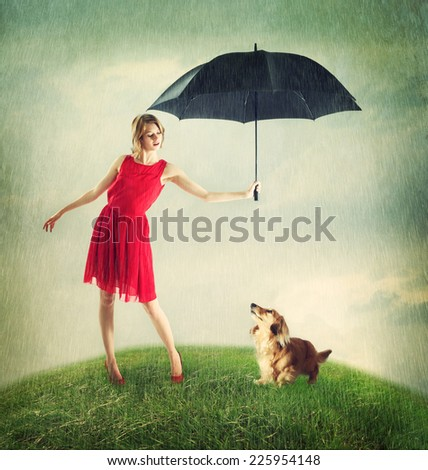 Young Woman in Red Dress Shielding Her Dachshund Dog from the Weather - stock photo
