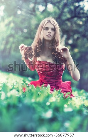 Young woman in red dress sitting on grass and looking aside. - stock photo