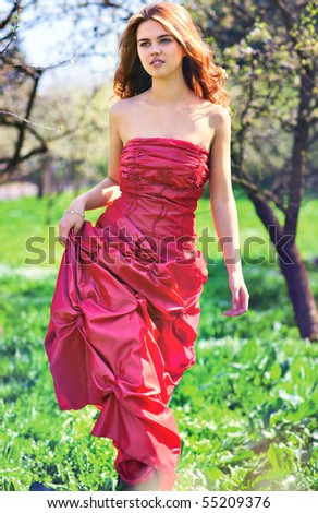 Young woman in red dress walking in garden. - stock photo