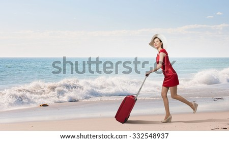 Young woman in red dress with red luggage