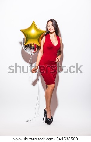 young woman in red dress with shaped balloon smiling over white background