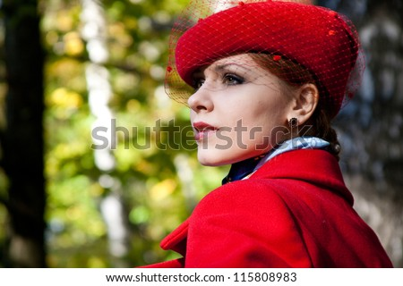 Young woman in red hat and red coat looking at something.