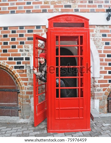 young woman in red hat look out from phonebox - stock photo