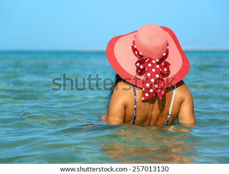 Young woman in red hat on the beach