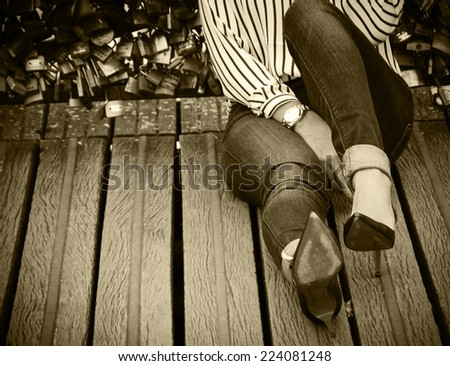 Young woman in red high heel shoes sitting on Love locks bridge in Paris. Retro aged photo. Sepia. Shadowed angles. - stock photo