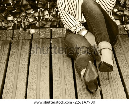 Young woman in red high heel shoes sitting on Love locks bridge in Paris. Retro aged photo. Sepia. - stock photo