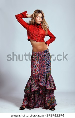 young woman in red leather jacket and floral print skirt studio shot - stock photo