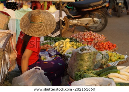 Young woman in red selling vegetables  at the street market in Kyaukme Myanmar (Burma) - stock photo
