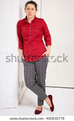 Young woman in red shirt lean against wall - stock photo