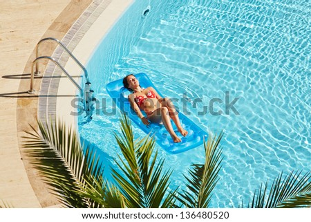 Young woman in red swimsuit sunbathes lying on inflatable mattress on water near to edge of pool - stock photo