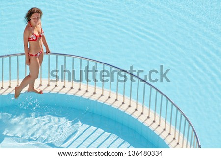 Young woman in red swimsuit walks on ledge separating two pools - stock photo