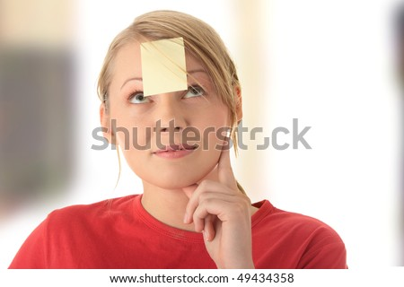 Young woman in red tshirt with yellow sticky note on forehead. - stock photo