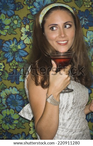 Young woman in retro outfit holding cocktail - stock photo