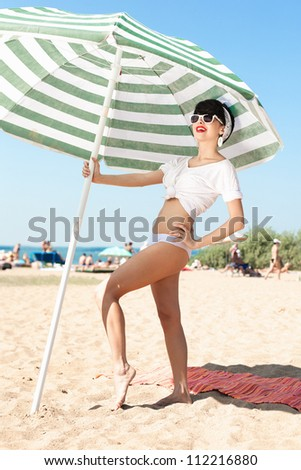 young woman in retro style by color parasol on the beach - outdoors - stock photo