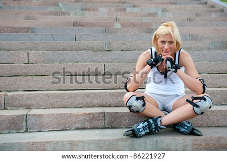 Young woman in roller skates sitting on the stairs - stock photo