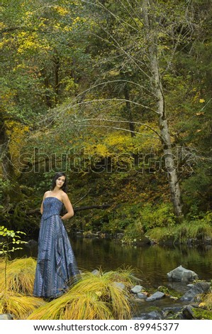 Young Woman in Romantic Woodlands near an autumn stream - stock photo