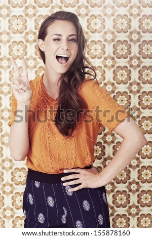 Young woman in 1970's fashion giving peace sign - stock photo