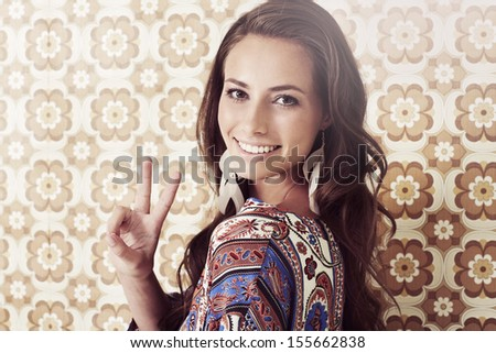 Young woman in 1970's fashion giving peace sign, smiling - stock photo