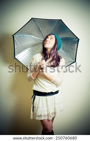 Young woman in 70s hippie style posing looking up with umbrella vintage color effect - stock photo