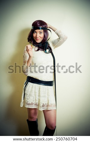 Young woman in 70s hippie style smiling and posing with 35mm movie film around head vintage color effect - stock photo