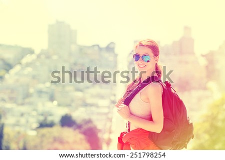 Young woman in San Francisco city with beautiful beaming smile backlit by warm glow of sun shining down on summer day. Positive emotions face expression. Instagram style yellow filter image  - stock photo