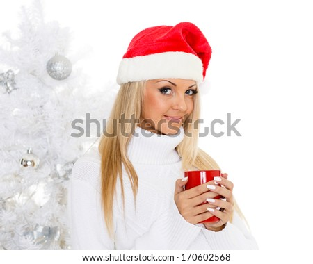 Young woman in Santa Claus cap  with red cup stands near Christmas tree on a white background. - stock photo