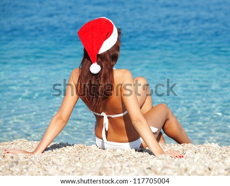 Young woman in santa hat sitting on the beach. Christmas vacation - stock photo