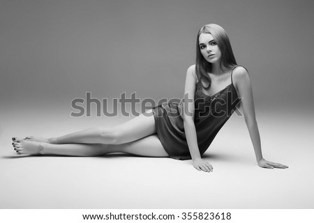Young woman in sexy underwear on floor studio black and white