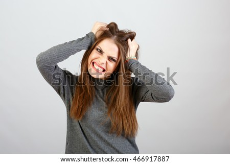 Young woman in shock, holding hands your hair
