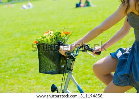 Young woman in short grey dress with long hair rides a bicycle with basket and flowers tour summer city park, look and smile on flowers bouquet - stock photo
