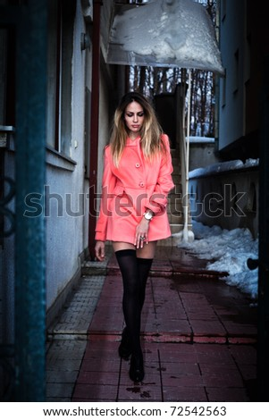 young woman in short pink coat and black stockings walking from house, winter dusk