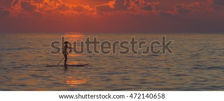 Young woman in silhouette paddle boarding at sunrise.