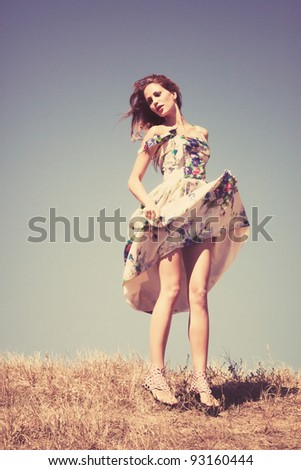 young woman in silk dress on top of the hill  sky in background, retro colours, grain added - stock photo