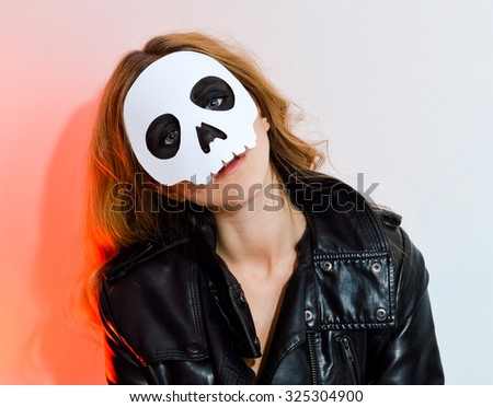 Young woman in skull mask; face of a young woman in paper halloween mask