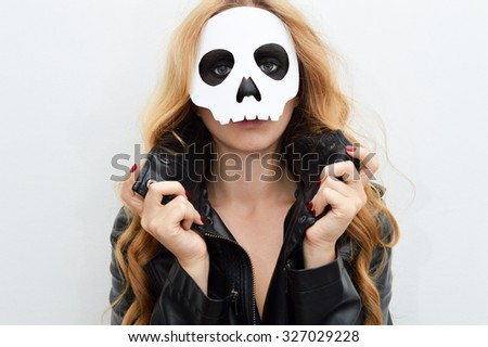 Young woman in skull mask; face of a young woman in paper halloween mask - stock photo