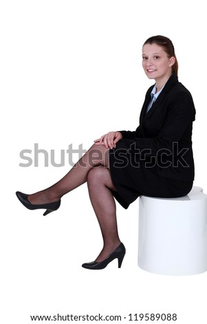 Young woman in smart suit sitting on a stool - stock photo