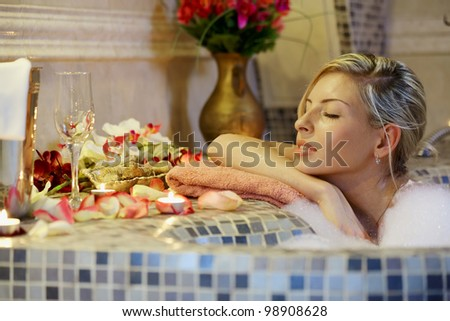 Young woman in spa bathroom in bath with water