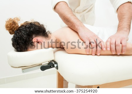 Young woman in spa getting a  body relaxing massage by male masseur - stock photo