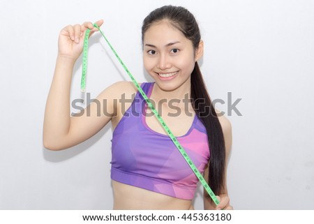 Young Woman in sport bra measuring her body with tape isolated on white - stock photo