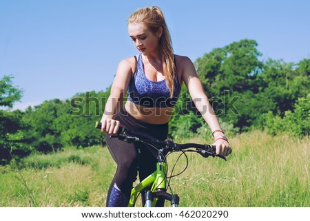 Young woman in sport wear posing, outdoor on the bicycle