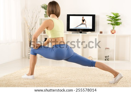 Young woman in sports clothes, athletic build, photographed from behind, exercise in the room, in front of the TV. - stock photo