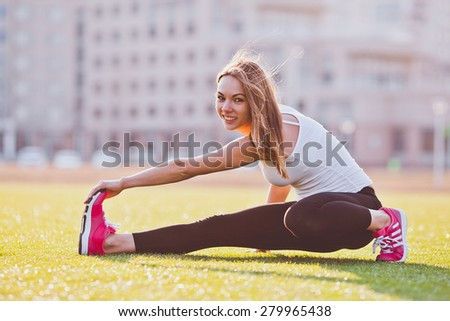 Young woman in sportswear with long hair stretching on a field in a campus. Holding her leg to stretch well. Sunny and bright photo. Concept of healthy lifestyle - stock photo
