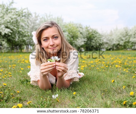 young woman in spring park among flowers