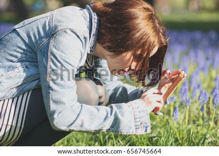 Young woman in spring park taking photo of blue flowers on mobile phone