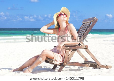 young woman in straw hat and bikini sitting on beach chair